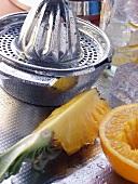 Lemon squeezer, orange, pineapple and ice cubes