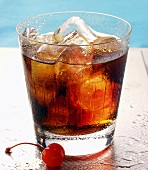 Drink with rum, orange and ice cubes; cocktail cherry