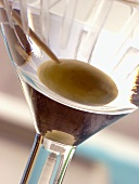 Martini with green olive in glass (detail)