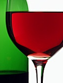 Red wine glass in front of red wine bottle (close-up)