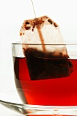 Removing tea bag from cup of hibiscus tea