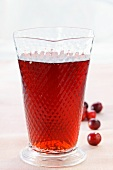 Cranberry juice in glass; fresh cranberries