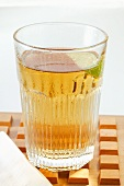 Apple juice with wedge of lime in glass