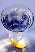 Glass of mineral water in blue; wedge of lemon