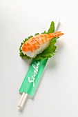 Nigiri sushi with shrimp on shiso leaf; chopsticks