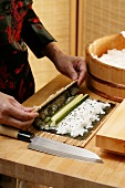 Preparing rolled sushi with cucumber