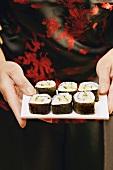 Hände servieren Maki-Sushi