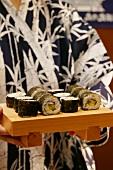 Person in kimono serving maki-sushi