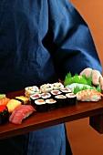 Person serving sushi platter