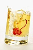 Ginger Ale with cocktail cherry splashing out of glass