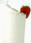 Milk splashing out of glass with strawberry