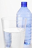 Mineral water in glass in front of plastic bottle