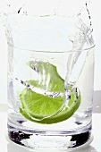 Pouring water into a glass with a slice of lime