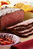 Roast beef on chopping board; tortilla chips