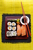 Assorted sushi on red platter; soy sauce