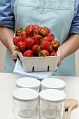 Woman holding punnet of strawberries; jam jars