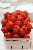 Fresh strawberries in cardboard punnet; jam jars; sugar