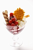 Sundae with raspberry ice cream, cream, wafers & sprinkles