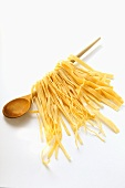 Home-made pasta hanging on kitchen spoon