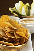 Tortilla chips in wooden bowl; dips; raw vegetables