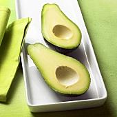 Zwei halbe Avocados auf weisser Platte; grüner Untergrund