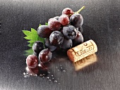 Wine cork and red grapes