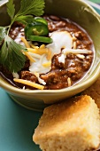 Chili con carne with cheese and sour cream; corn bread
