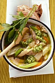 Chicken soup with pearl barley and vegetables in saucepan