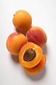 Vier Aprikosen, eine davon halbiert