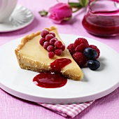 White chocolate tart with berries and fruit sauce