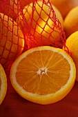 Half an orange in front of oranges in net