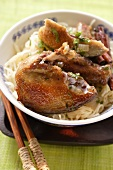 Roast pigeon on noodles in Asian bowl; chopsticks
