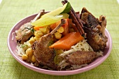 Roast pigeon with vegetables and cinnamon sticks on noodles