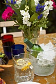 Table with white wine, lemon water, flowers, glasses (outside)