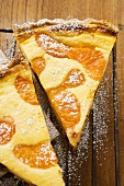 Two pieces of apricot tart with icing sugar