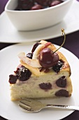 Piece of cheesecake with cherries and coconut shavings