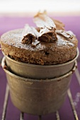 Chocolate soufflé with chocolate curls and icing sugar