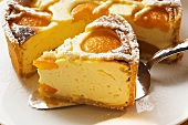 Piece of apricot cheesecake in front of cut cake