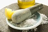 Coarse salt with pestle, lemon and olive oil