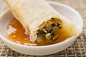 Dipping spring roll in chili sauce