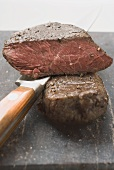 Beef steaks, one with a piece cut off, with knife
