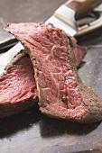 Two slices of beef steak beside knife