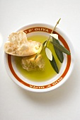Olive oil in bowl with white bread and olive branch