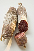 Two whole Italian salamis, one with a piece cut off