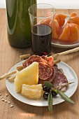 Salami, cheese, olives & grissini on plate, tomatoes, wine