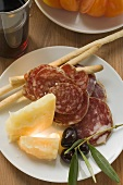 Salami, cheese, olives and grissini on plate