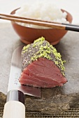 Raw tuna fillet with poppy seeds and lime zest, rice
