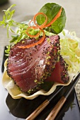 Raw tuna fillet with poppy seeds, with salad garnish