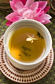Jasmine tea in small bowl in front of water lily