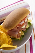 Ham, cheese, tomato and onion in sub sandwich with crisps